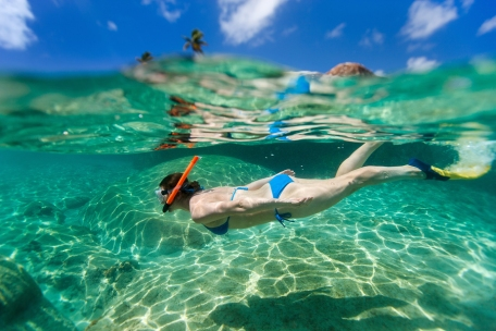 young woman snorkeling in turquoise ocean at Cari
