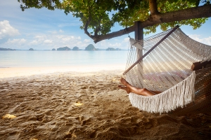 Young lady relaxing in hammock on the sandy beach