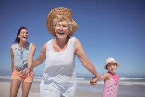 Cheerful multi-generation family at beach during sunny day